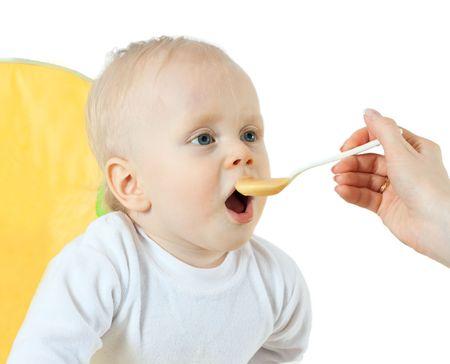beautiful baby eating - isolated on white background photo