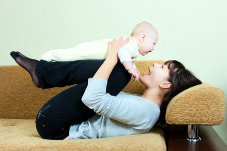 happy family: mother and baby on the sofa - playing and smiling photo