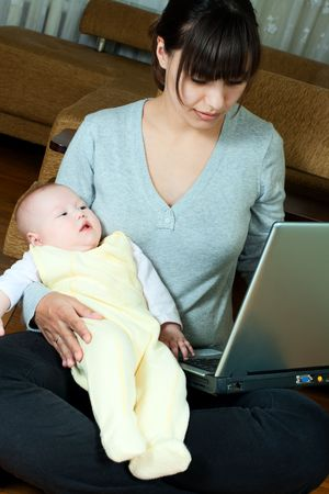 young mother working on laptop and holding her baby photo