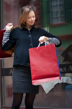 beautiful young woman with shopping bags looking to watch photo