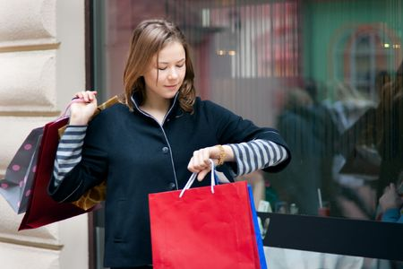 beautiful young woman with shopping bags looking to a watch photo