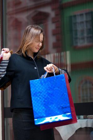 window shopper: beautiful young woman with shopping bags looking to a watch