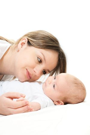 happy family home: mother and baby lying on the bed and playing Stock Photo