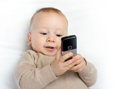 cute baby boy playing with mobile phone on white - closeup photo