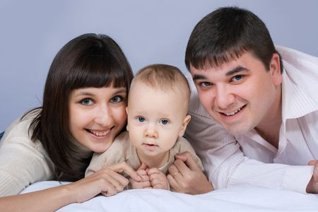 happy family home: father, mother and baby boy lying on the floor and smiling Stock Photo - 6570467