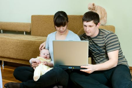 happy family home: father, mother and baby working on laptop photo