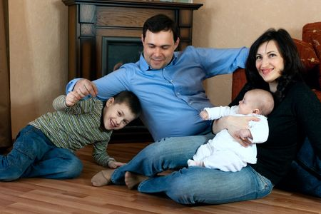 happy family home: father, mother, son and baby lying on the floor and playing Stock Photo