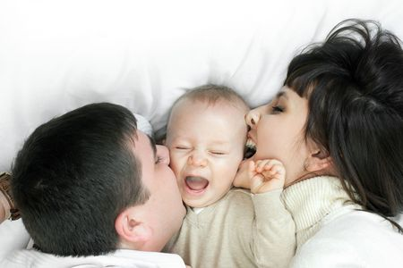 happy family home: father, mother and baby lying on the floor and playing photo