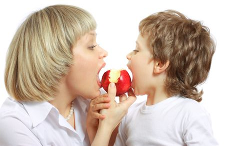woman and little boy playing and eating an apple Stock Photo