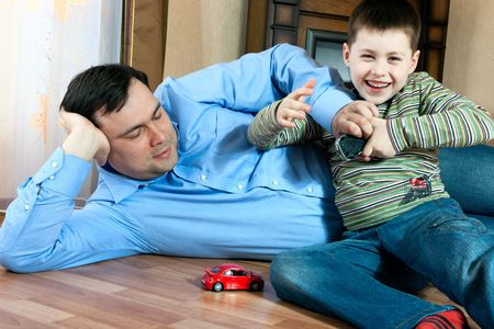 happy family home: father and son playing on the floor