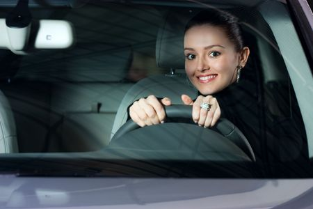 young beautiful woman driving a car and smiling Stock Photo