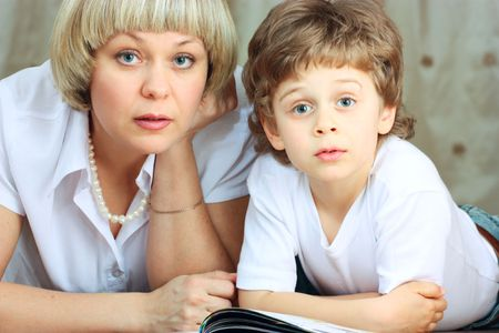 woman and little boy lying down on the floor and reading a book photo