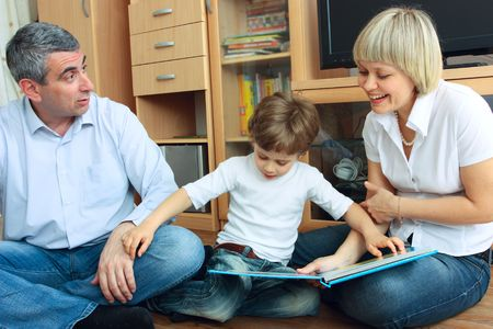 man, woman and little boy sitting on the floor in living room and reading book Stock Photo - 6755579