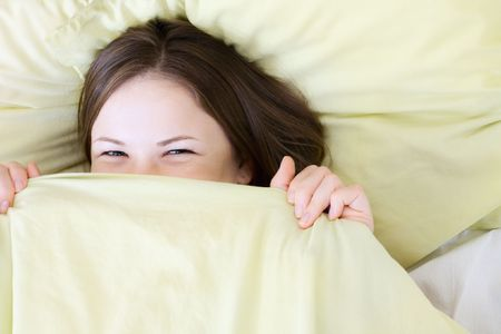 young beautiful woman smiling in the bed photo