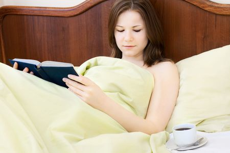 young beautiful woman with book and cup of coffee in the bed photo