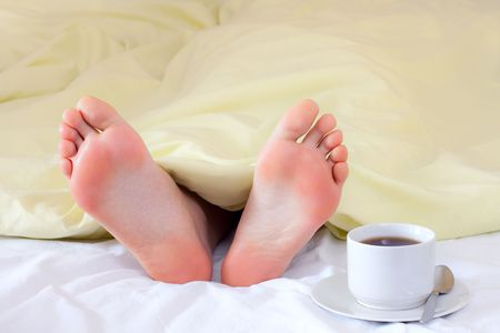 A couple of tiny feet the blanket - and cup of coffee - good morning photo