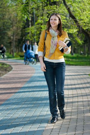 young cute woman with books walking in the park Stock Photo