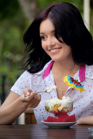 young beautiful woman eating an ice cream in cafe photo
