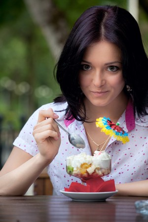 young beautiful woman eating an ice cream in cafe