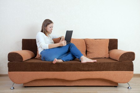 Young beatiful woman with laptop on the sofa