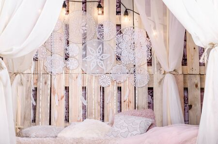 Bedroom loft design with bed soft pillows canopy swing with white tulips dream catcher with feathers and pearls hanging on a wooden background