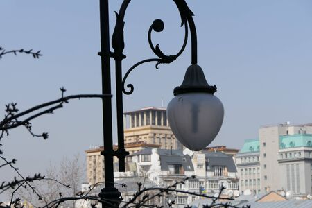 Beautiful, black, cast-iron street lamp of a classic design with a white ceiling.