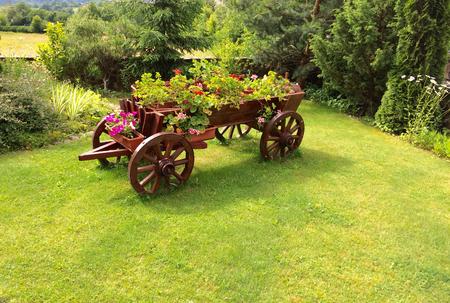 Flower bed an old wooden cart, flowerbed grass lawn garden design element, outdoor rustic landscaping