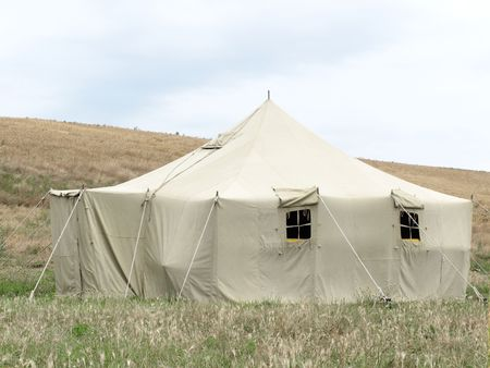 The image of millitary tent under the meadow photo
