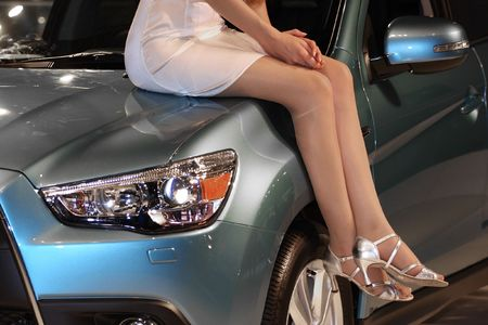 bonnet: The image of girl sits on the car bonnet Stock Photo