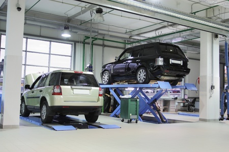 service lift: Cars on the elevator in a repair garage Editorial