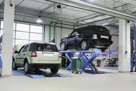 garage automobile: Voiture sur l'ascenseur dans un garage de r�paration