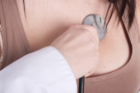 hand brings stethoscope to the woman chest Stock Photo - 12628960