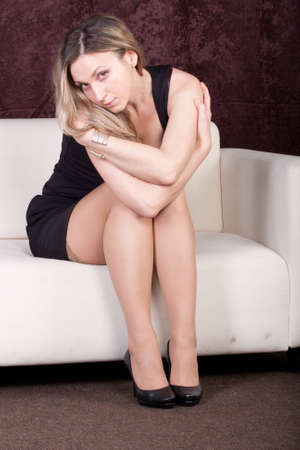 Sad girl sits on a sofa photo