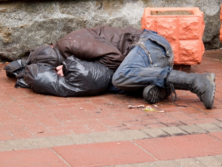 beggar: Homeless man sleeps on a pavement
