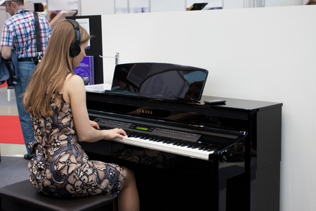 MOSCOW - MAY 18, 2012: Visitor of NAMM Musikmesse Russia musical exhibition tests grand pianos in Moscow on May 18, 2012 Stock Photo - 13796050