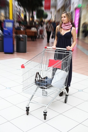 Young girl with a shopping trolley in supermarket photo