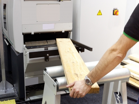The image of a worker near the woodworking machine photo