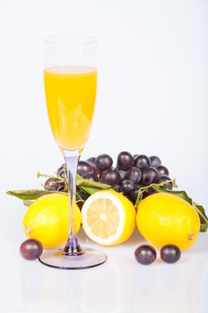 lemon, wine glass with juice and grapes under the white background Stock Photo - 17939354