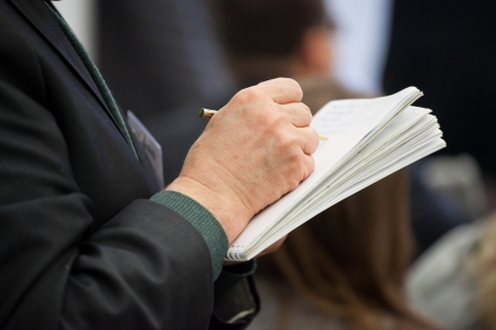 Hand of an elderly businessman and note-book in it Stock Photo - 17939344
