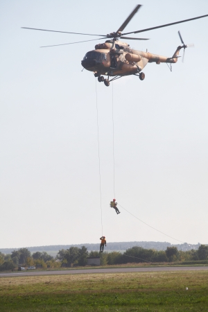 abseil: Two man climb from helicopter down a rope