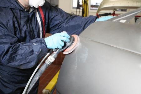 car body: Painter polishs a car body component Stock Photo