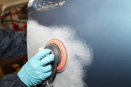buff: Painter polishs a car body component Stock Photo