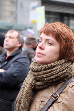 downtrodden: MOSCOW - MARCH 15: Woman leastens to a speech on meeting in the time of protest rotest manifestation of muscovites against war in Ukraine and Russias support of separatism in the Crimea, Circular Boulevards in Moscow, Russia on March, 15, 2014. It was no