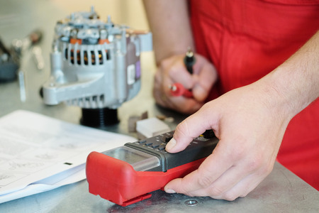 Hands of mechanic restores a generator photo