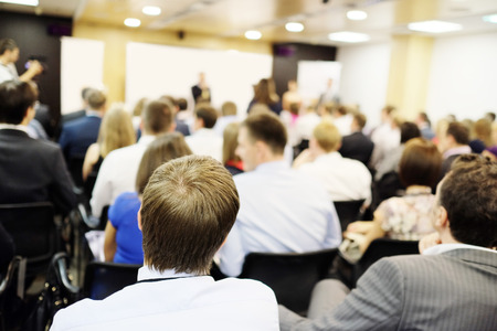 acting: The audience listens to the acting in a conference hall