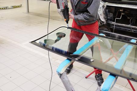 arbeiten, um die Kleb- und Dichtstoff auf der Windschutzscheibe gelten