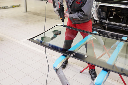 working to apply the adhesive sealant on the windshield Stock Photo