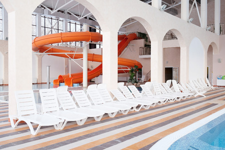 daybed: Swimming pool and many white empty chaise-longue