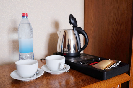 electric tea kettle: Two empty white cups in the hotel room