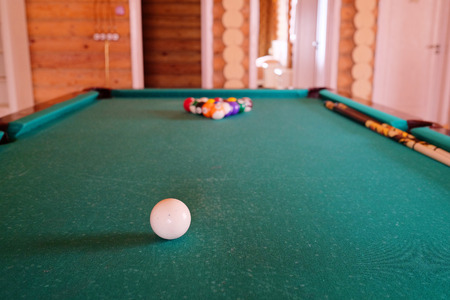 snooker hall: White billiard ball on a green billiard table Editorial